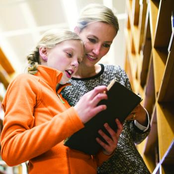 Mother with Daughter in Library Reading Book
