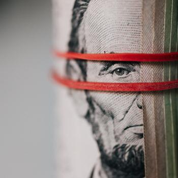 pic of Abe Lincoln money roll with red rubber band around it