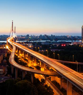 Speeding Cars in City at Dusk
