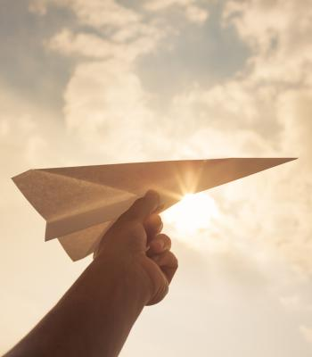 Paper airplane with sky in background